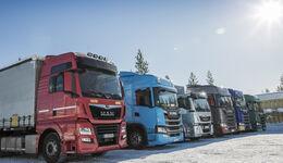 MAN- und Scania-Fahrzeuge bei einem Test im Winter vor blauem Himmel.