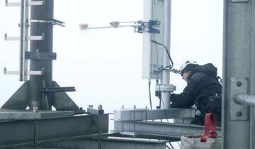Telekom-Mitarbeiter installiert 5G-Antenne auf dem Fernsehturm Hamburg